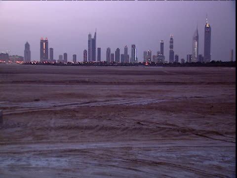 City skyscrapers in distance across wasteland at sunset Dubai