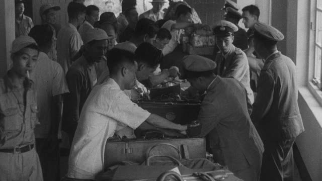 stockvideo's en b-roll-footage met 1949 montage city street and customs officers inspecting luggage and patting down passengers / singapore - 1949