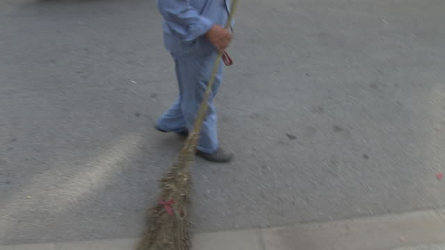 ms city street cleaner sweeping curb with broom/ shanghai, china - cleaner stock videos and b-roll footage
