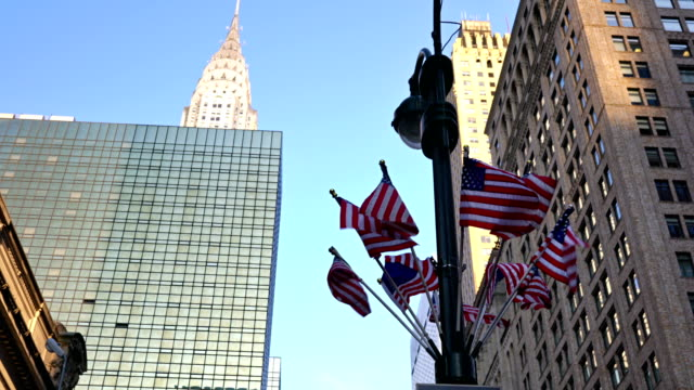 city street, empire state building and american flags. panning - national flag stock videos and b-roll footage
