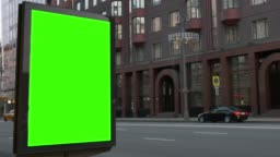 City street. Evening. Showcase with a large green screen. Cars are coming.