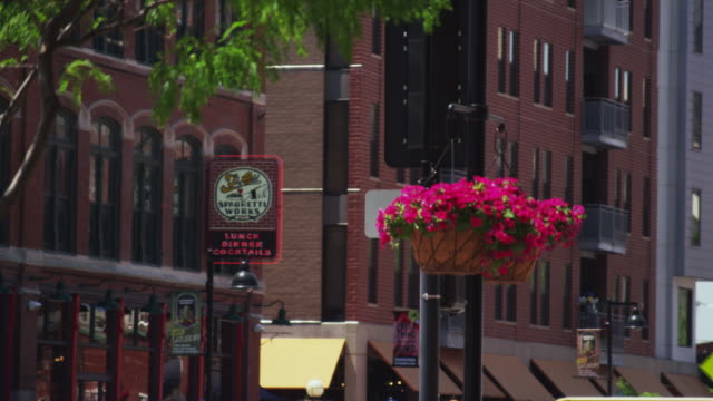 city street featuring brick buildings and beautiful flowers in hanging baskets - dissolvenza in chiusura video stock e b–roll