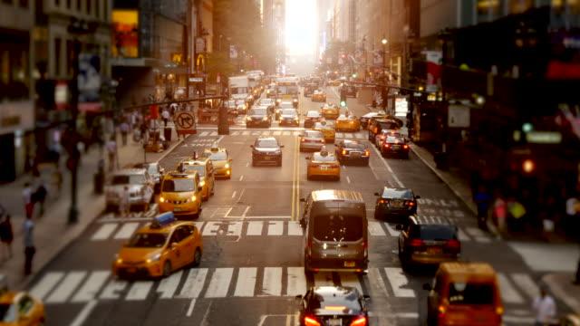 city street landmarks scene of urban metropolis background. rush hour traffic and commuters scene - イエローキャブ点の映像素材/bロール