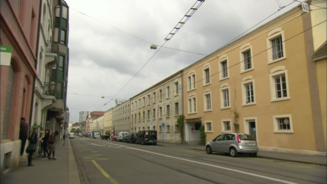 ws city street lined with buildings that are all three stories tall / basel, switzerland - campo totale video stock e b–roll