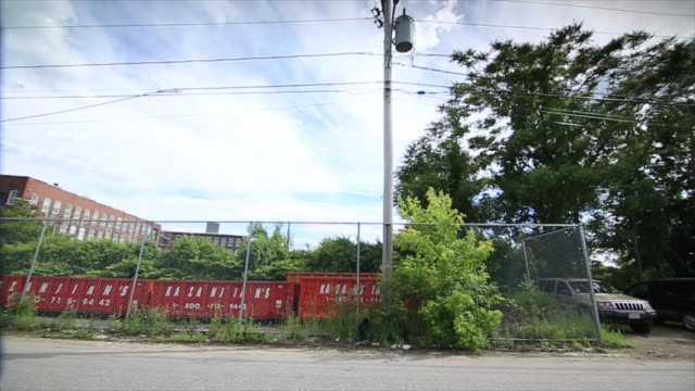 city street lot w/ large garbage receptacles dump truck behind fence midrise brick building parks cars service station garage brick building w/... - lowell stock videos & royalty-free footage