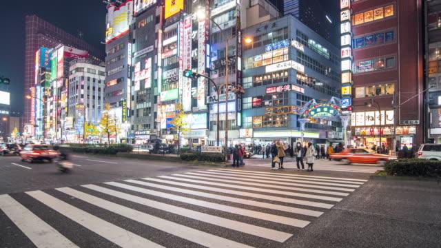stadtstraße nachtleben mit masse menschen auf zebra zebrastreifen in der stadt von shinjuku, tokyo, japan - spruchband stock-videos und b-roll-filmmaterial