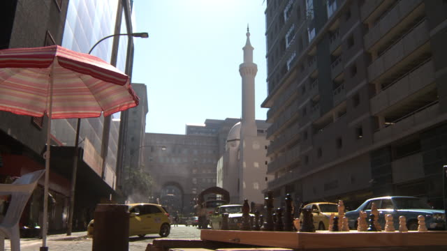 vidéos et rushes de city street, parked cars, kerk street mosque minaret & dome, chair & open umbrella left, mid-rise building right, chessboard w/ pieces fg. - port saïd