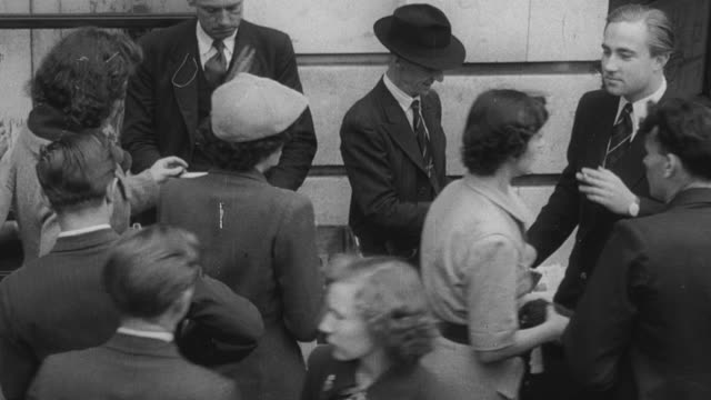 1949 MONTAGE City street, pedestrians buying newspapers, opening and reading them / London, England, United Kingdom