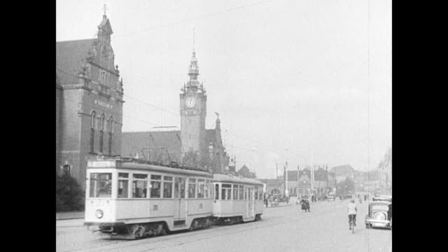 ws city street scenes tram passing reveal city hall tower bg ws waterfront dlugie pobrzeze boulevard along water crane distant - 1937 stock videos and b-roll footage