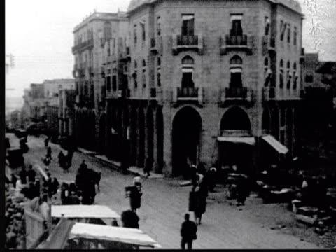 1925 b/w montage city street. traffic policeman directs cars / beirut, lebanon - 1925年点の映像素材/bロール