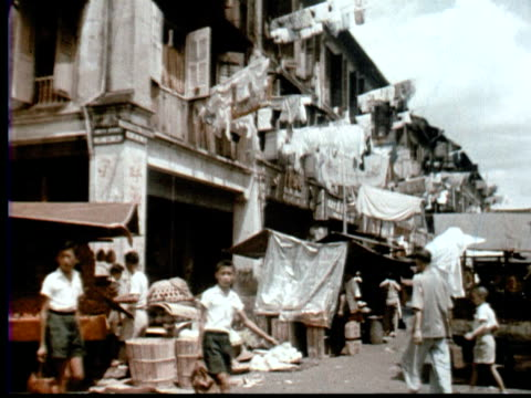 1957 MONTAGE City street w/ laundry hanging. Pedestrians, cars + bicycles / Singapore / AUDIO