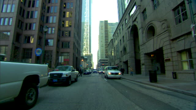 """city street w/ multi-story buildings on either side, vehicles parked & following, trees w/ bare branches, """"one way"""" sign, skyscraper bg. urban,... - one way stock videos & royalty-free footage"""