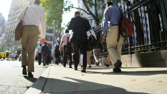 city sunlight commuters and rush hour traffic manhattan - new york stato video stock e b–roll