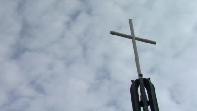 """""""City top crucifix, simple and white, backdrop of fast moving clouds"""""""