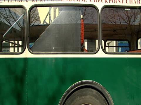 stockvideo's en b-roll-footage met city tour bus pulls up track left from car past bus through streets of berlin - ruimte exploratie