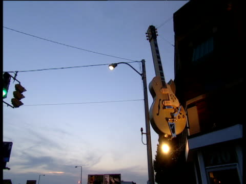 city traffic at dusk with large guitar on side of building pan right to sun studios sign - memphis tennessee stock-videos und b-roll-filmmaterial