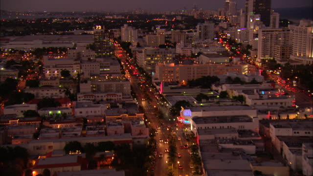 city traffic bustles through miami beach at sunset. - nightlife stock videos & royalty-free footage