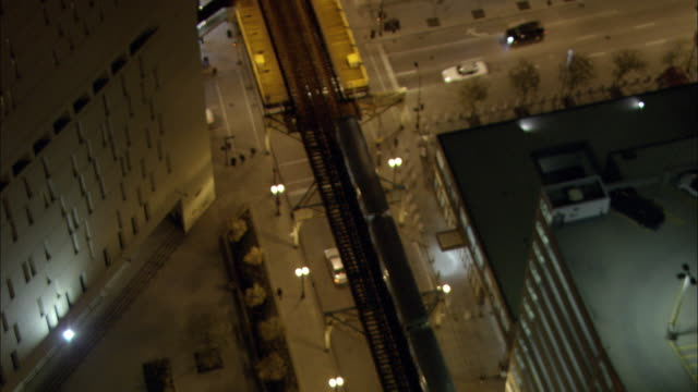 city traffic crosses under the chicago 'l' at night. - chicago 'l' stock videos & royalty-free footage
