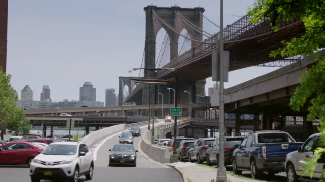 City traffic exits ramp with view of Brooklyn Bridge standing tall in background.