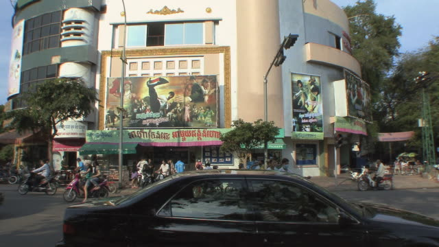ws city traffic in front of movie theater with large billboards, phnom penh, cambodia - phnom penh stock videos and b-roll footage