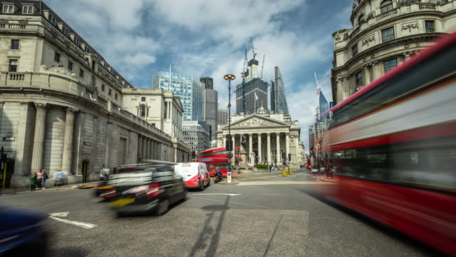 city traffic moves rapidly past the bank of england and the royal exchange with modern skyscrapers and building developments under construction in the background - investment stock videos & royalty-free footage