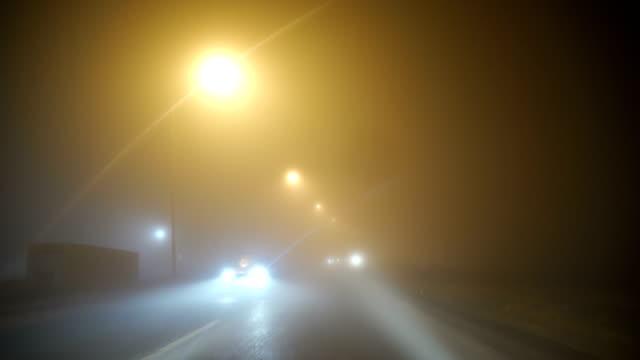 vidéos et rushes de trafic de la ville sur une nuit brumeuse - phare avant de véhicule