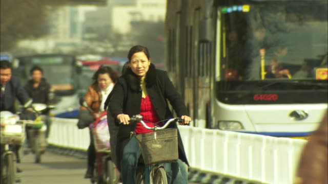 vídeos de stock, filmes e b-roll de ms pan city traffic with people riding bikes, beijing, china - plano americano