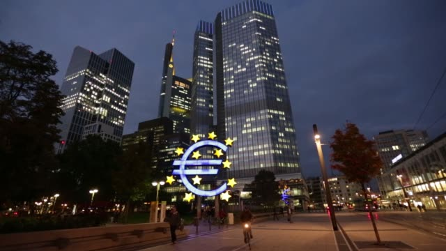 A city tram and pedestrians pass through a plaza past the euro sign sculpture outside the European Central Bank headquarters at dusk in Frankfurt...