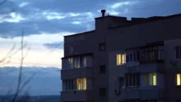 City twilight scene, windows of residential apartment building at dusk