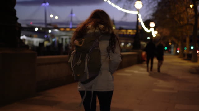 city walking, rear view young woman with a rucksack. - teenager stock videos & royalty-free footage