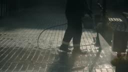 City worker clean sidewalk brick block closeup hosing with powerful jet water 4K