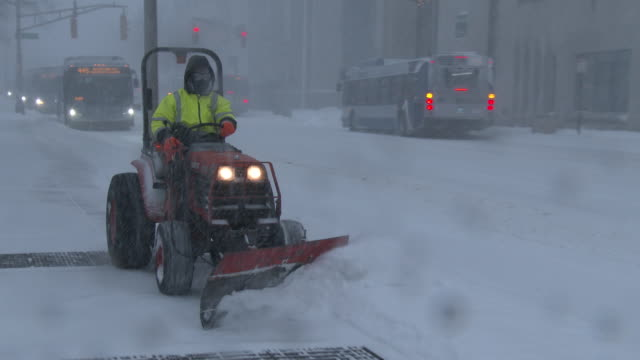A city worker rides a snow plow and clears the sidewalks of deep snow in Waterbury Connecticut during a powerful nor'easter