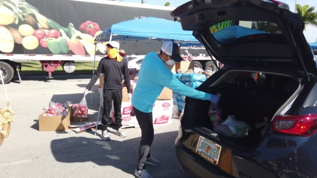 city workers and volunteers place items of food into vehicles during a food distribution setup at hialeah gardens high school on april 22 2020 in... - hialeah stock videos & royalty-free footage