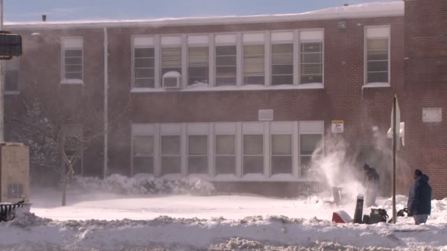 City workers clearning snow in strong winds the day after the blizzard of 2013