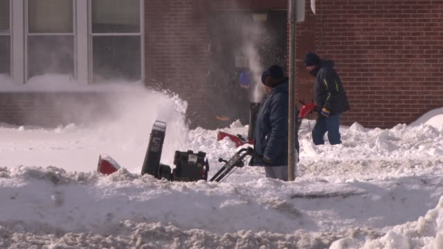 city workers clearning snow in strong winds the day after the blizzard of 2013 - 2013 stock-videos und b-roll-filmmaterial