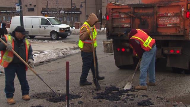 stockvideo's en b-roll-footage met wgn city workers filling in potholes on january 11 2014 in chicago illinois - bouwvoertuig