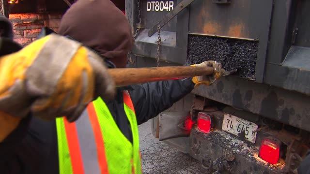 vídeos de stock, filmes e b-roll de / city workers filling potholes on chicago streets on in chicago illinois - caldeirão água parada