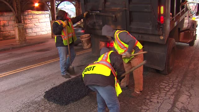 stockvideo's en b-roll-footage met / city workers filling potholes on chicago streets on in chicago illinois - bouwvoertuig