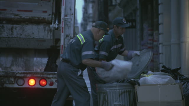 city workers jump off a garbage truck and empty trash along a street in soho. - dustman stock videos & royalty-free footage