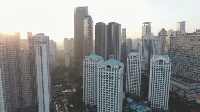 city's buildings at sunrise, aerial revealing from down to up camera angle then move from right to the left - jakarta stock videos & royalty-free footage
