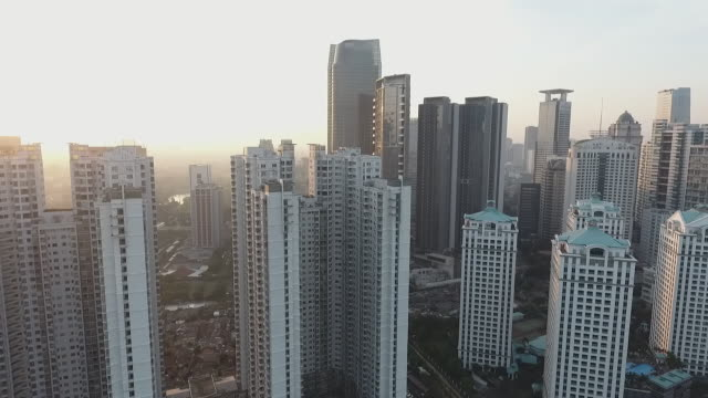 city's buildings at sunrise, aerial revealing from right to the left - jakarta stock videos & royalty-free footage