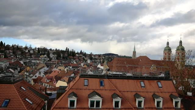 vidéos et rushes de cityscape and abbey of st gallen with storm cloud - flèche clocher