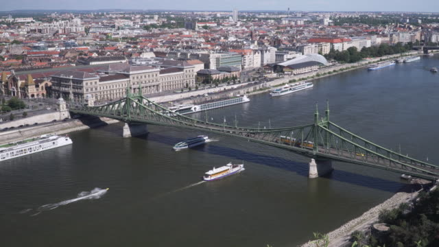 cityscape and landscape high angle view on national landmark: liberty bridge along danube river with traveling boat in budapest from the viewpoint on gellért hill on a sunny day of summer and blue sky, hungary. - liberty bridge budapest stock videos & royalty-free footage