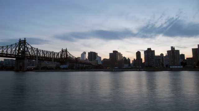 ws, t/l, cityscape and queensboro bridge over east river toward manhattan, day to night, new york city, new york, usa  - クイーンズボロ橋点の映像素材/bロール