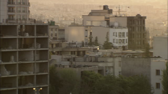 ws pan cityscape at late afternoon, shabby crumbling buildings and apartment buildings / teheran, iran - iran stock videos and b-roll footage