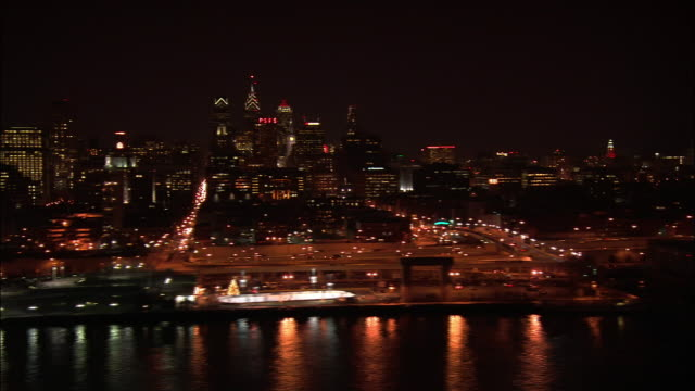AERIAL, cityscape at night along river, Philadelphia, Pennsylvania, USA