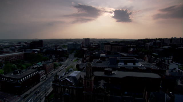 a cityscape at sunset features a church in the foreground. available in hd. - newcastle upon tyne video stock e b–roll