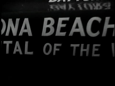 1956 b/w montage ws ha pan td ms cu cityscape by beach, novelty car driving along beach, large sign detailing speed records / daytona beach, florida, usa / audio - scrittura occidentale video stock e b–roll
