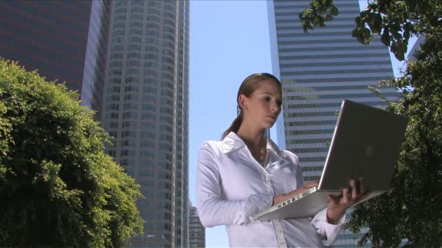vídeos y material grabado en eventos de stock de cityscape in downtown laone business woman talking on a mobile phone with reading a newspaper in a park - sólo mujeres jóvenes
