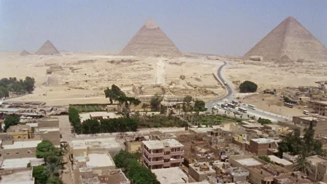 aerial ws cityscape near great sphinx and three giza pyramids / giza, egypt - piramide struttura edile video stock e b–roll